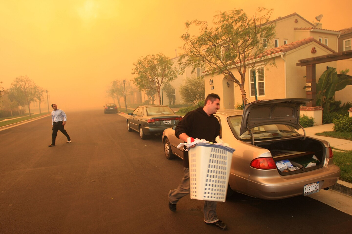 A man carries a white plastic hamper to the trunk of his car on a street where a deep orange smoke is everywhere.