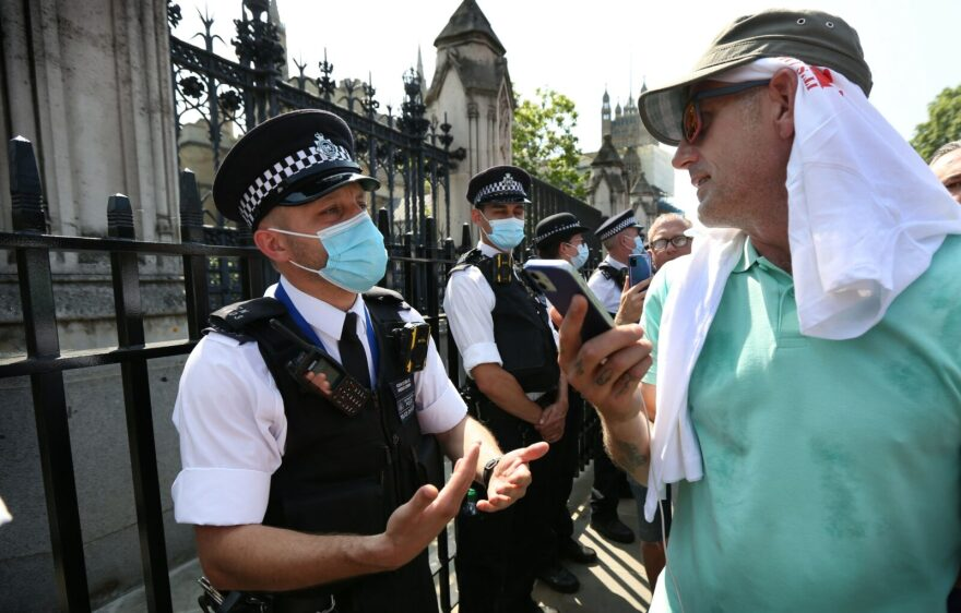 Protesters confront a police line outside the House of Commons during a freedom protest in London, England.