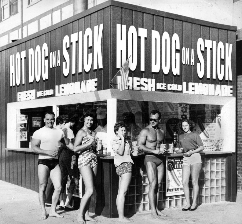 """a black and white photo of 3 young women and 2 young men, all in bathing suits, standing in front of a stand with a sign that reads """"Hot Dog on a Stick"""""""