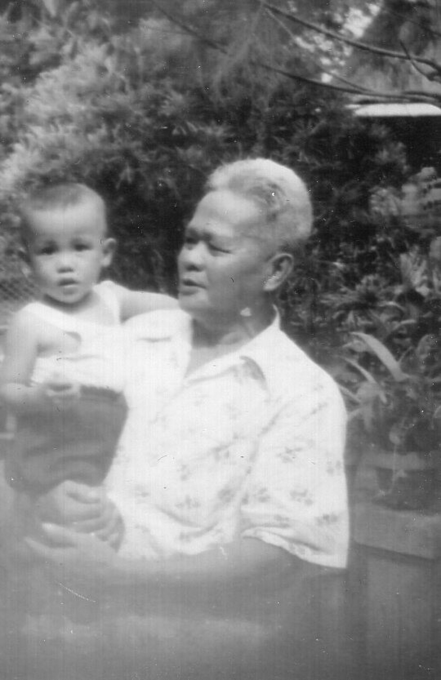 Black and white photo of Rene Trinidad with his grandfather Telesforo Trinidad in the Philippines.
