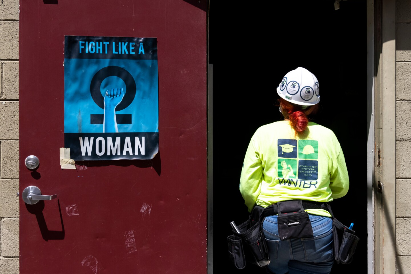 """The back of a woman wearing a hard hat with a red-haired pony tail, yellow sweatshirt and jeans as she walks through a doorway. On one door is a poster saying """"fight like a woman""""."""