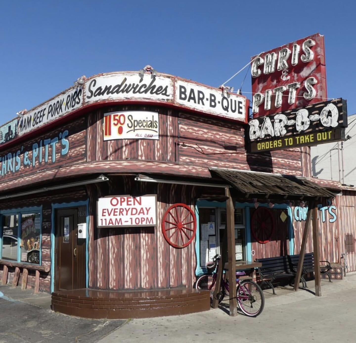 """The exterior of a brown building made to look like a log-cabin. The sign reads """"Chris' & Pitt's Bar-B-Q. Ham, Beef, Pork, Ribs, Sandwiches."""""""