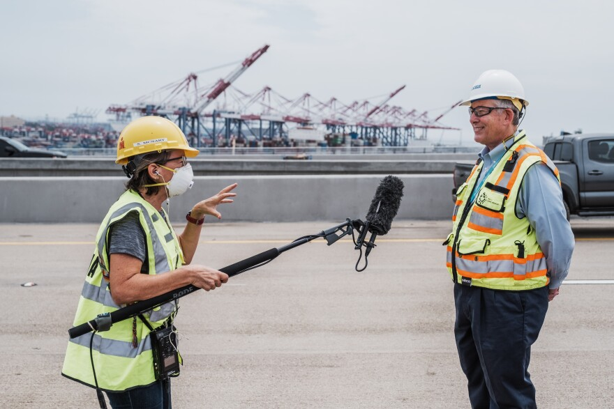 A reporter in a yellow hard hat and safety vest holds a boom mic during an interview with a man in a white hard hat and yellow safety vest. The port is behind them.