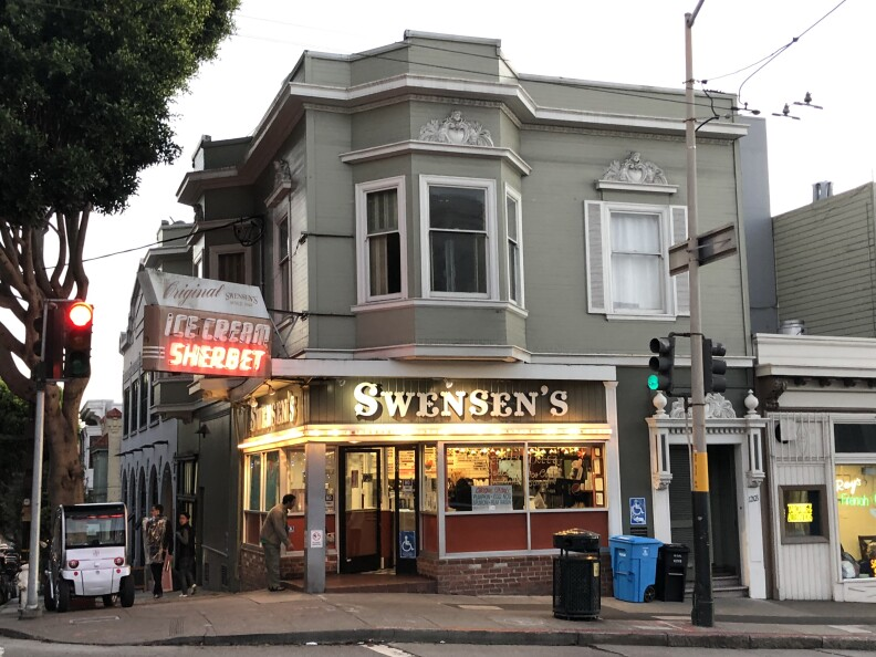 """a two-story, gray Victorian building with a sign that reads """"Swensen's. ice cream. sherbet."""""""