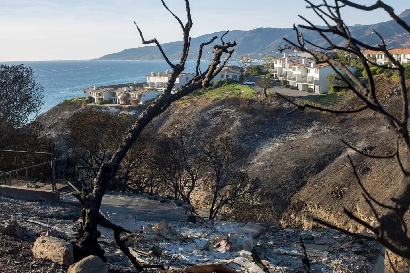 In the foreground, bare burned hills. In the background, Tows of untouched townhomes and the ocean.