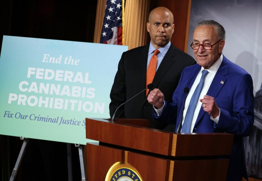U.S. Senate Majority Leader Charles Schumer (D-NY) (R), joined Sen. Cory Booker (D-NJ), speaks at a press conference on introducing legislation to end federal cannabis prohibition at the U.S. Capitol.