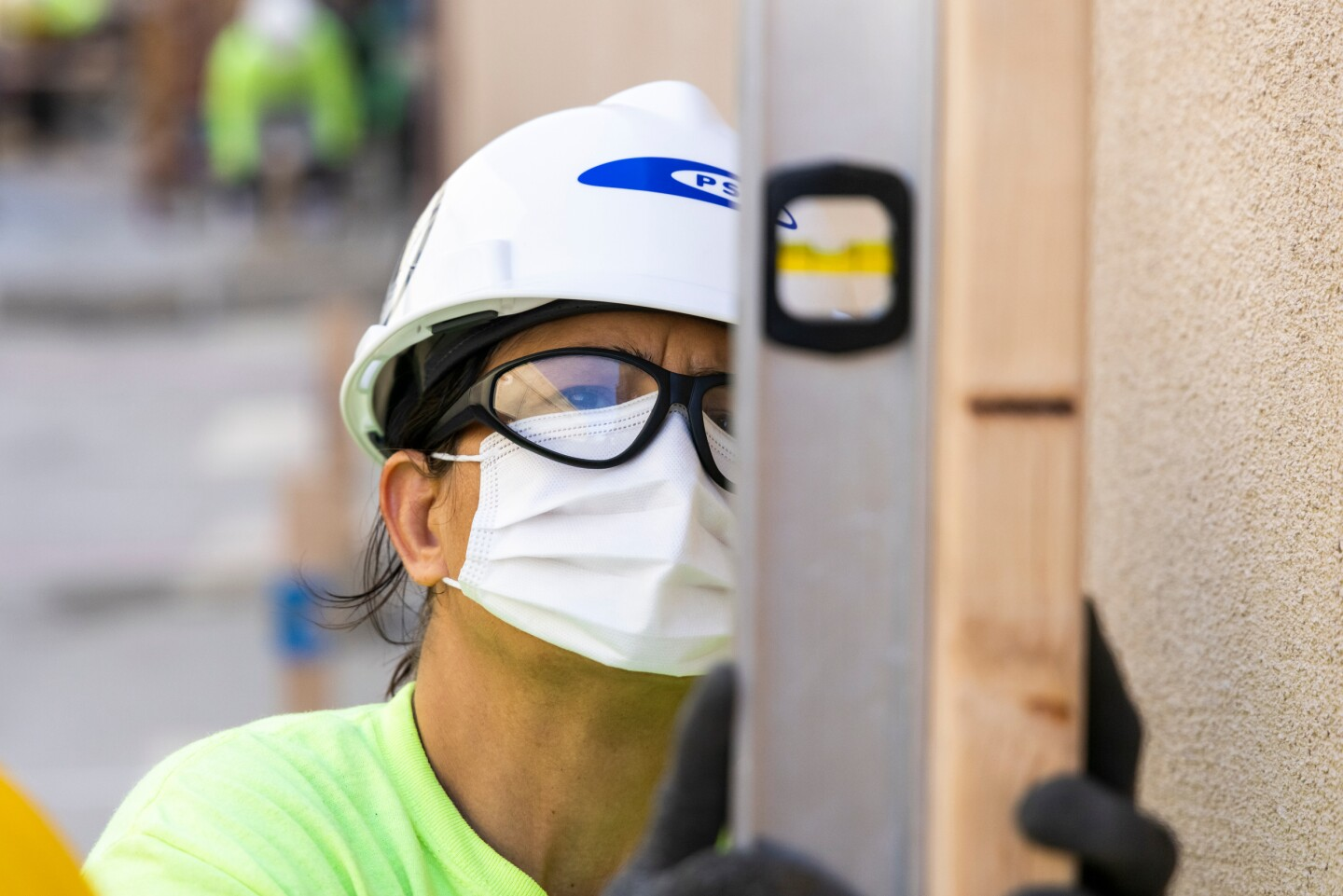 A woman wearing a hard hat, safety glasses and a mask looks at a leveling tool