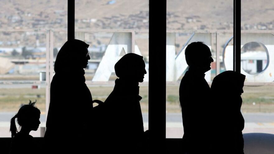 People leave to board a flight at the airport in Kabul on Monday. Leaving Afghanistan for the U.S. has become a huge challenge now that American troops and embassy staff have left the country.