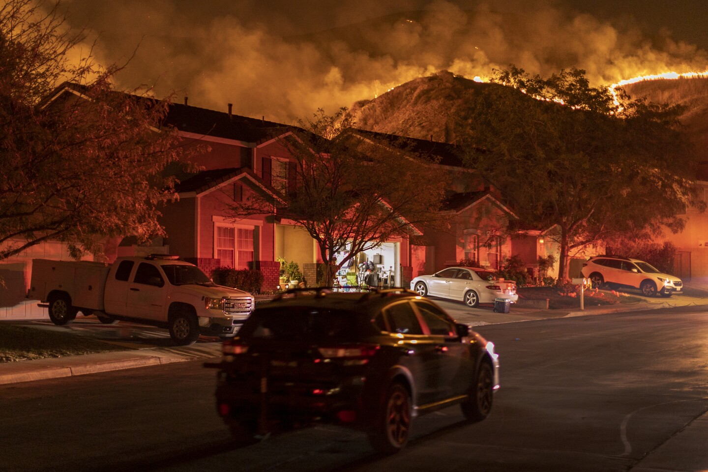 A neighborhood where heavy smoke and flames are heading over the ridge line has cars in driveways and one open garage.