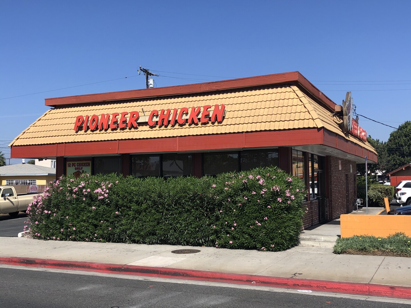 """a building with a brown roof with a sign on it that reads """"pioneer chicken"""""""