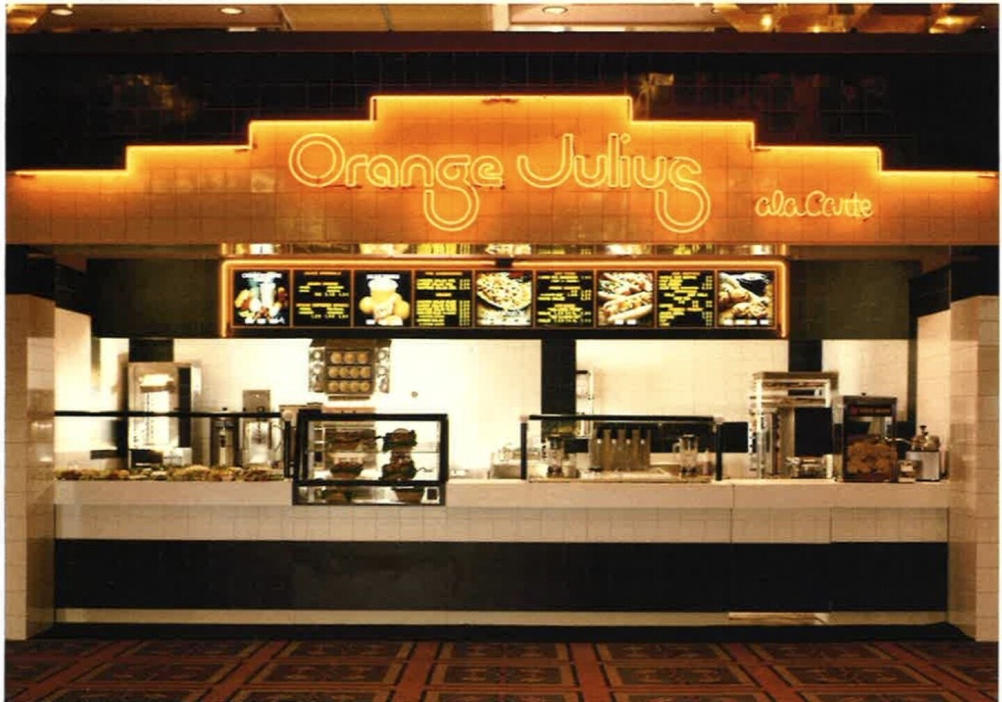 a fast food counter with a menu above it and above that a neon orange sign that reads Orange Julius