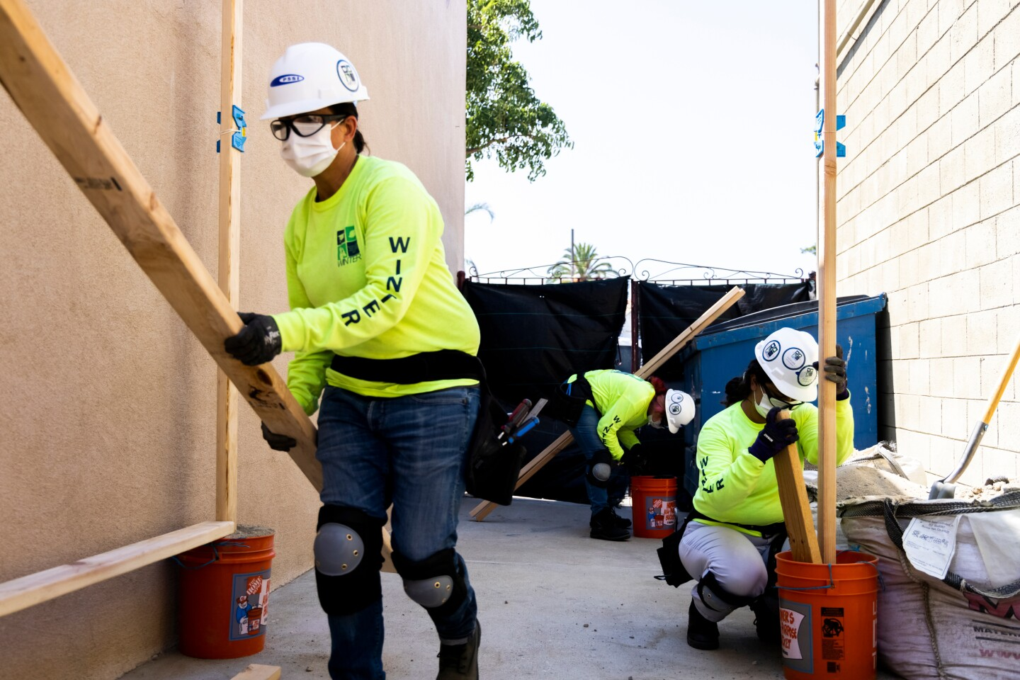 Women wearing white hard hats, safety glasses, white masks and yellow sweatshirts carry wood in a yard