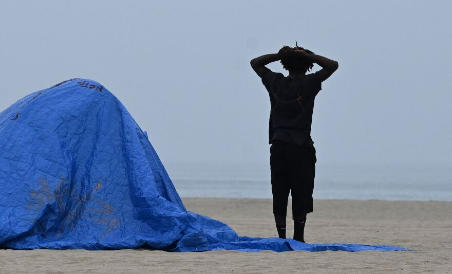 A man looks toward the ocean beside his tent as authorities prepare to clear homeless encampments at the Venice Beach Boardwalk ahead of the Independence Day holiday weekend, July 2, 2021 in Los Angeles, California.