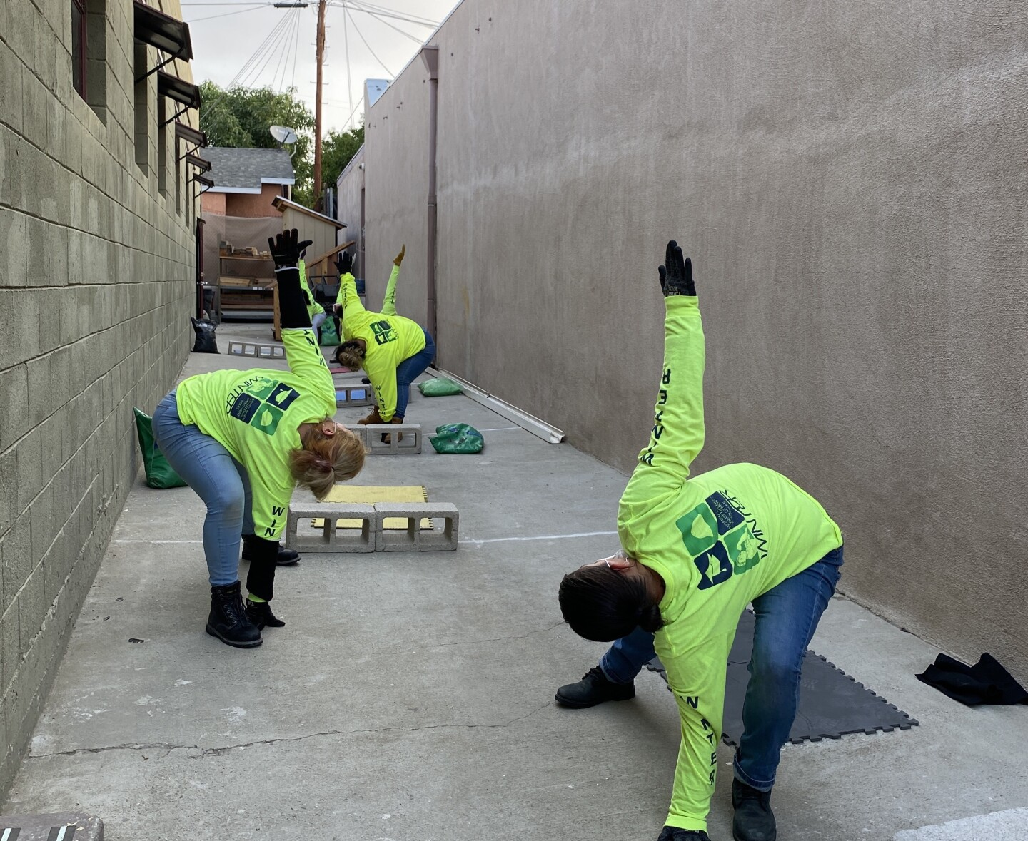 three women in a yard wearing yellow sweatshirts and jeans are exercising as cinder blocks lay around them